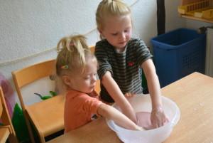 Kinder matschen in einem Topf