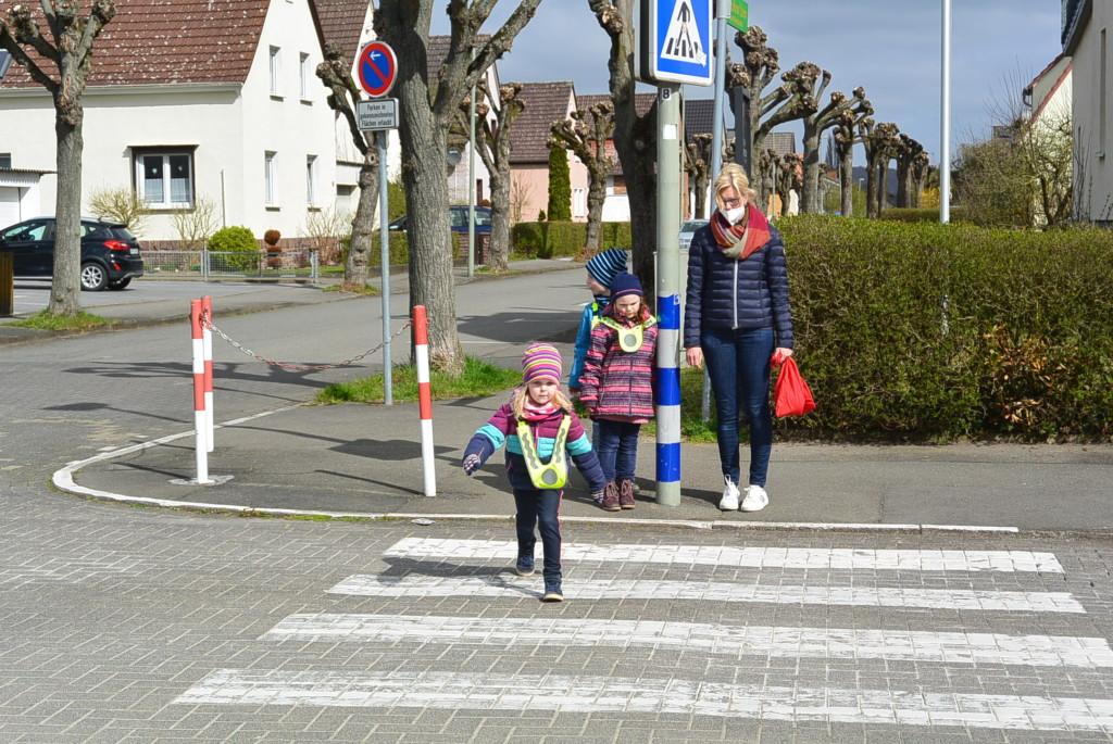 Kinder mit einer Erzieherin beim Überqueren der Straße